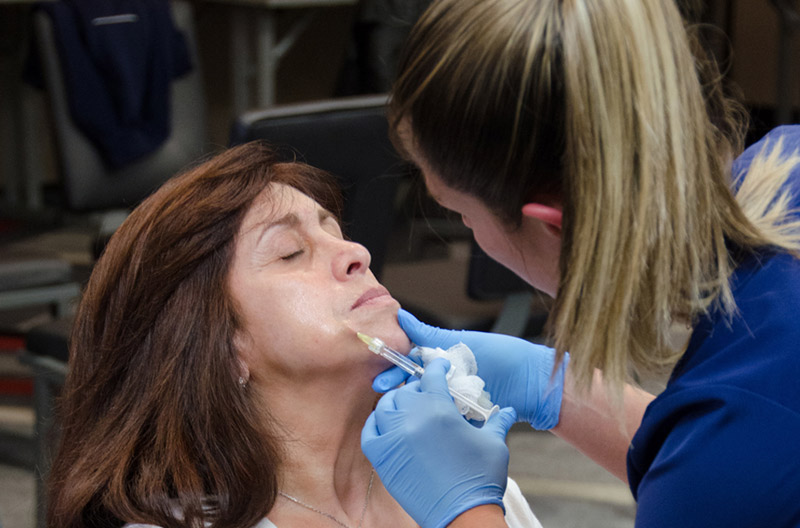 Doctor performing aesthetic injection on woman face