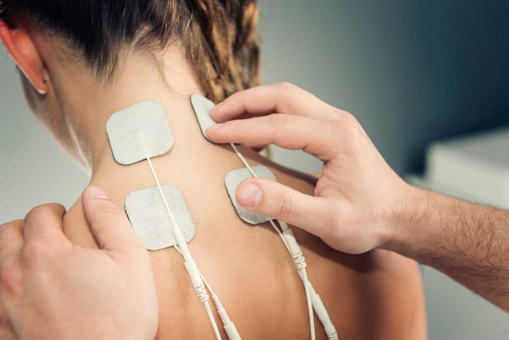 Physician placing TENS unit for upper back pain